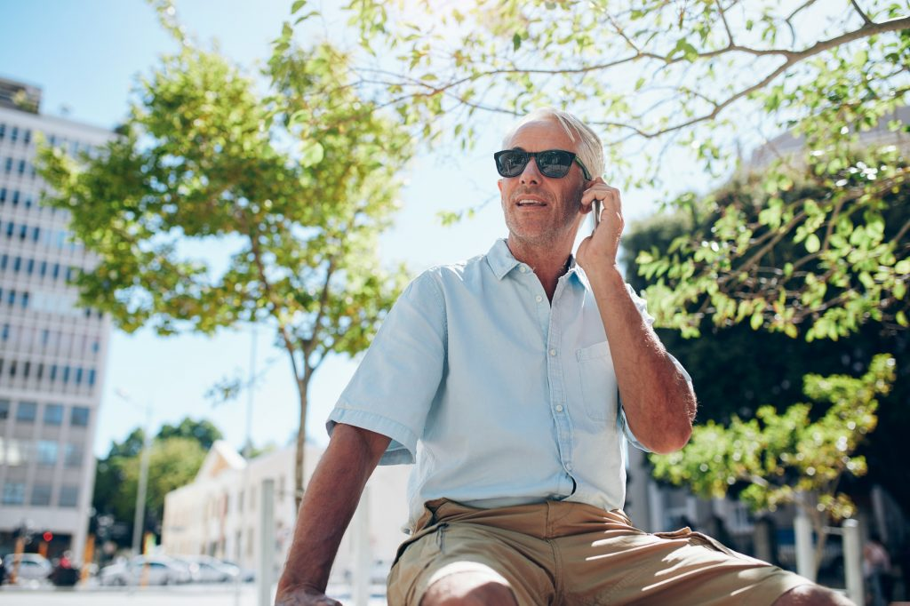Mature man sitting outdoors in the city making a phone call